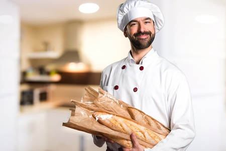 Happy young baker holding some bread in the kitchen Banco de Imagens
