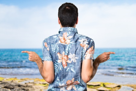 Handsome man with flower shirt pointing to the laterals having doubts at the beach