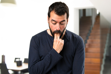 Handsome man with beard making vomiting gesture inside house Stock Photo