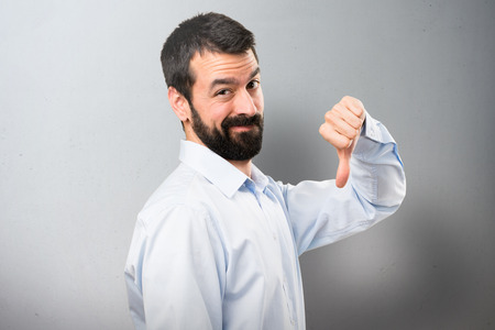 Handsome man with beard making bad signal on textured background