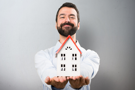 icone: Happy Handsome man with beard holding a little house on textured background Stock Photo