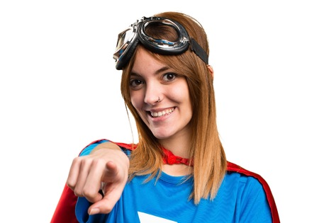 Pretty superhero girl pointing to the front
