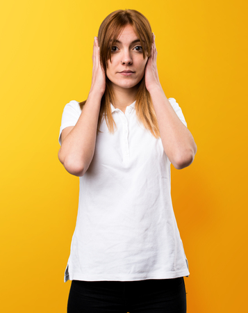 ignore: Beautiful young girl covering her ears on yellow background