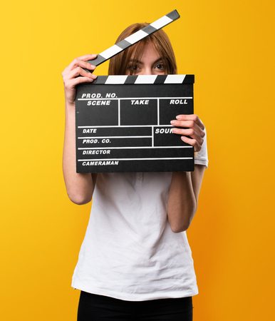 Beautiful young girl holding a clapperboard on yellow background Stock Photo