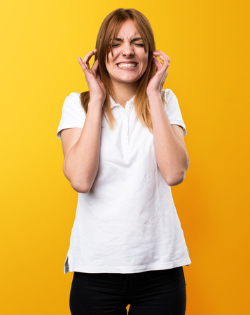 Beautiful young girl covering her ears on yellow background