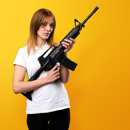 female police: Beautiful young girl holding a rifle on yellow background