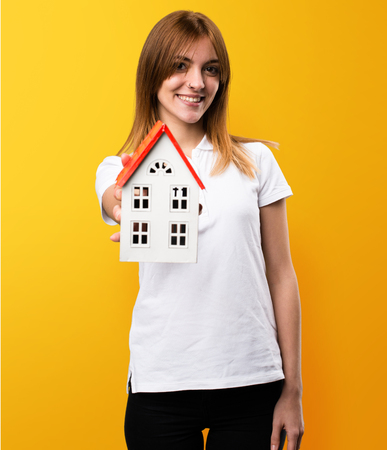 icone: Happy Beautiful young girl holding a little house on yellow background