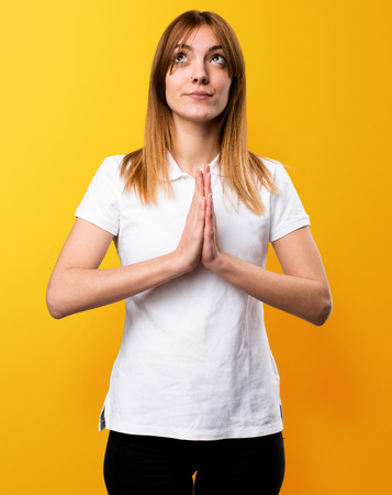 plead: Beautiful young girl pleading on yellow background Stock Photo