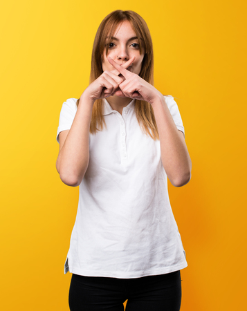 Beautiful young girl making silence gesture on yellow background