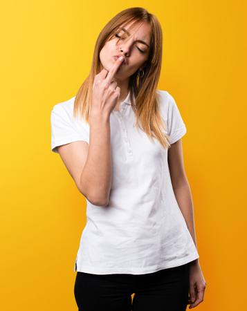 Beautiful young girl making horn gesture on yellow background