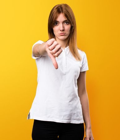 Beautiful young girl making bad signal on yellow background