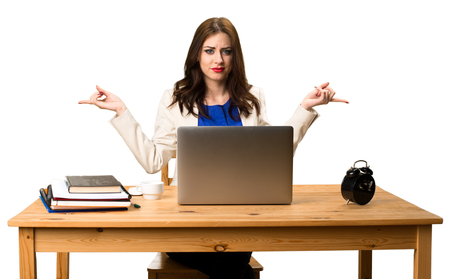 Business woman working with her laptop and pointing to the laterals having doubts