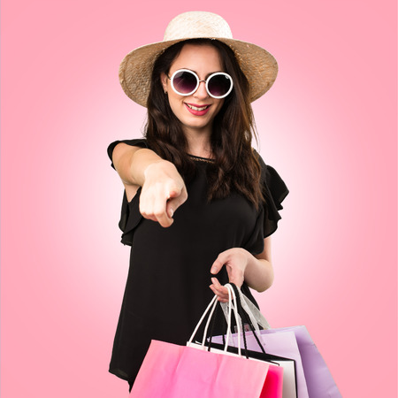 Beautiful young girl  with shopping bag pointing to the front on colorful background Stock Photo