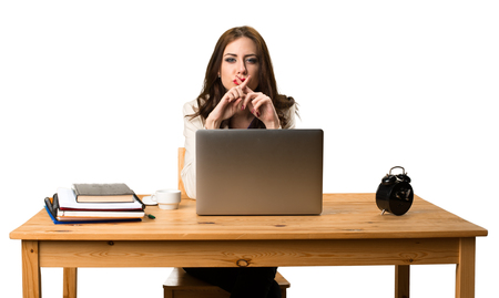 Business woman working with her laptop and making silence gesture