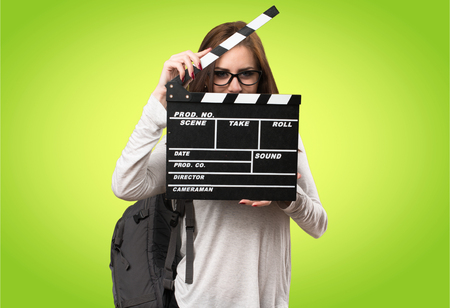 Student woman holding a clapperboard on colorful background