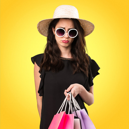 Sad beautiful young girl  with shopping bag on colorful background