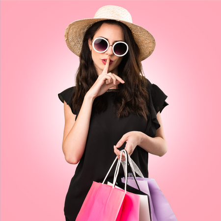 Beautiful young girl  with shopping bag making silence gesture on colorful background