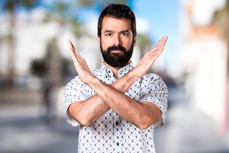 Handsome brunette man with beard making NO gesture