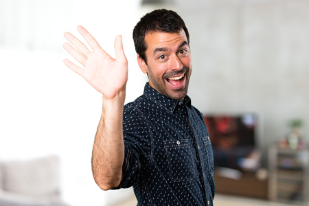 Brunette man saluting inside house