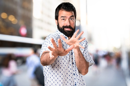 disgusted: Handsome brunette man with beard making stop sign Stock Photo