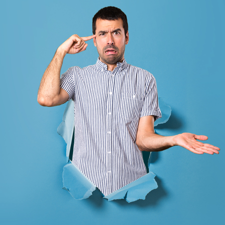 Handsome man making crazy gesture through a paper hole Stock Photo