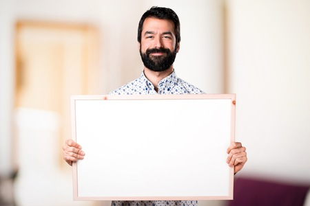 Handsome brunette man with beard holding an empty placard