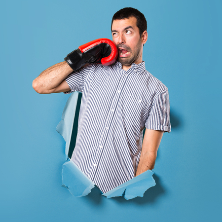 Handsome man with boxing gloves through a paper hole Stock Photo