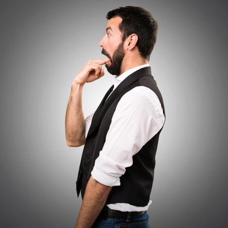 Cool man making vomiting gesture on grey background