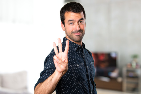 Brunette man counting three inside house