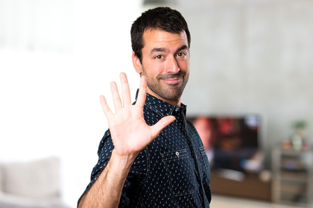 counting five: Brunette man counting five inside house Stock Photo
