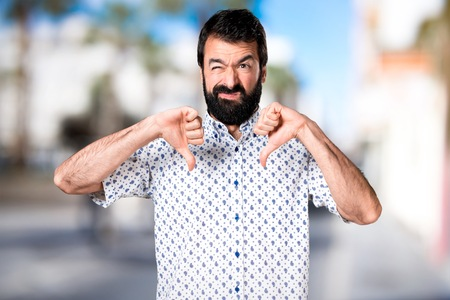 Handsome brunette man with beard making bad signal