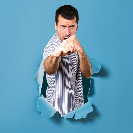 Handsome man fighting through a paper hole Stock Photo
