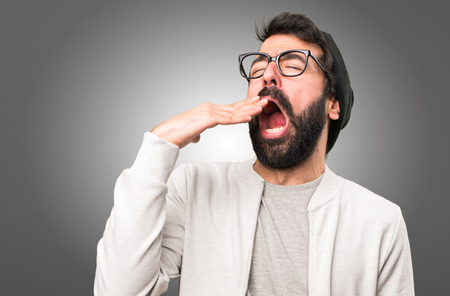 Hipster man yawning on grey background