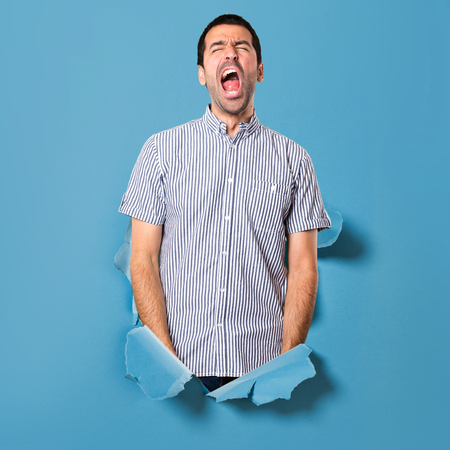 Handsome man yawning through a paper hole Archivio Fotografico