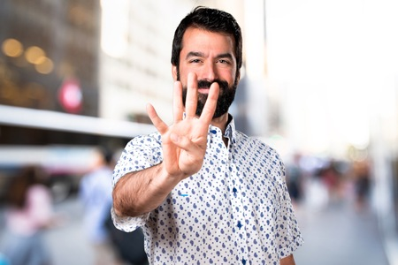 Handsome brunette man with beard counting four Stock Photo