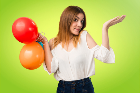 Beautiful young girl holding a balloon and making unimportant gesture on unfocused background