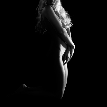 Artistic nude woman on black background
