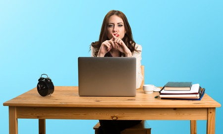 Business woman working with her laptop and making silence gesture on colorful background