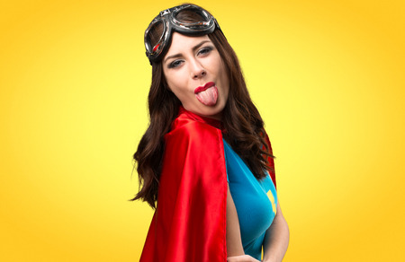 Pretty superhero girl taking out her tongue on colorful background Stock Photo