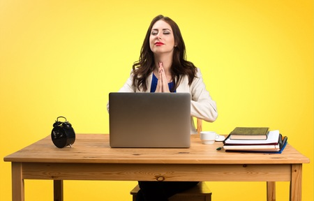 Business woman working with her laptop and in zen position on colorful background Stock Photo