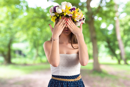 Girl with crown of flowers covering her eyes Stock Photo