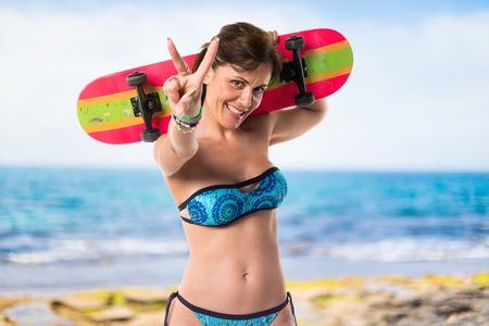 Woman in blue bikini with skate