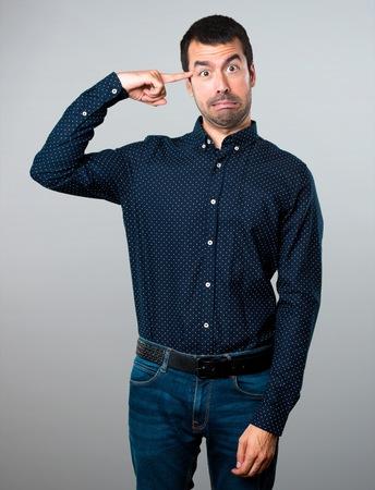 Handsome man making crazy gesture on grey background