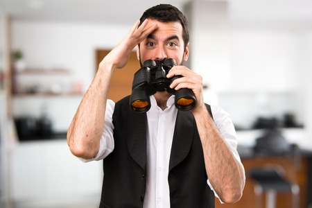Cool man with binoculars inside house