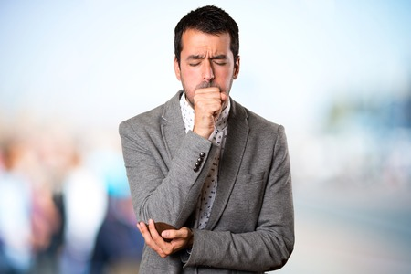 Handsome man coughing a lot on unfocused background Фото со стока