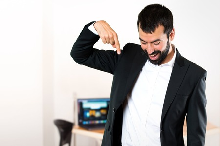Handsome businessman pointing down in the office