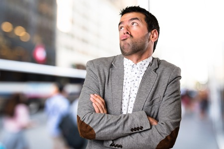 Handsome man making unimportant gesture on unfocused background Stock Photo