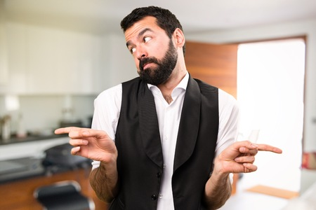 Cool man pointing to the laterals having doubts inside house Stock Photo