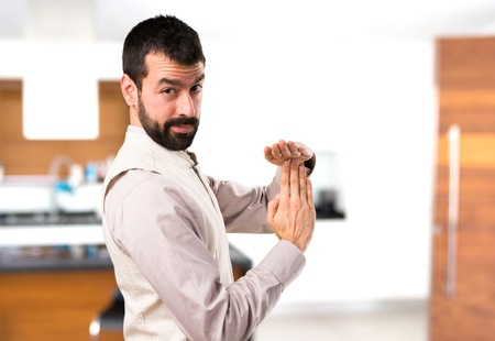 Handsome man with vest making time out gesture inside house