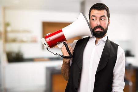 Cool man holding a megaphone inside house